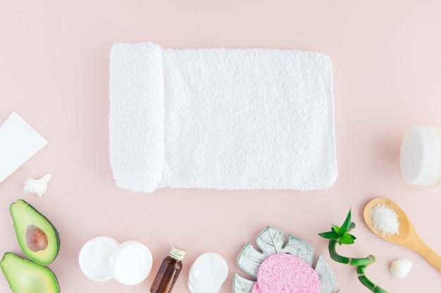 Vista piana e superiore dell'asciugamano bianco, barattolo di crema, foglie verdi e bambù, avocado sul rosa pastello