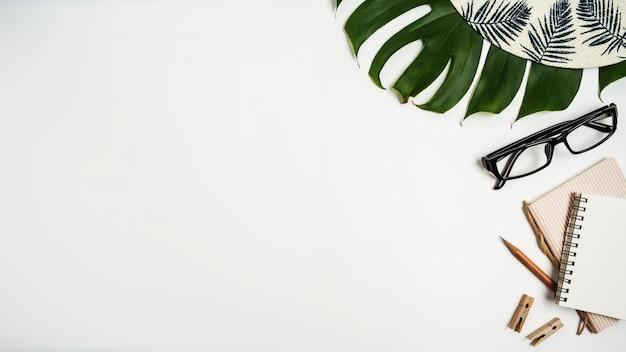 Vista piana, vista dall'alto dell'area di lavoro con occhiali da vista, taccuino, cappello, matita, foglia verde, scarpe e tazza di caffè su sfondo bianco.