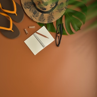Vista piana, vista dall'alto dell'area di lavoro con occhiali da vista, taccuino, cappello, matita, foglia verde, scarpe e tazza di caffè su sfondo marrone.