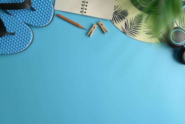 Vista piana, vista dall'alto dell'area di lavoro sfondo blu. estate elegante viaggiatore blogger concetto.