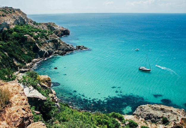 Vista pittoresca del mare pulito blu, rocce, barca galleggiante e alberi verdi.