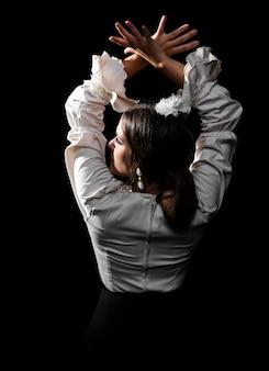 Vista posteriore ballerina di flamenco alzando le mani