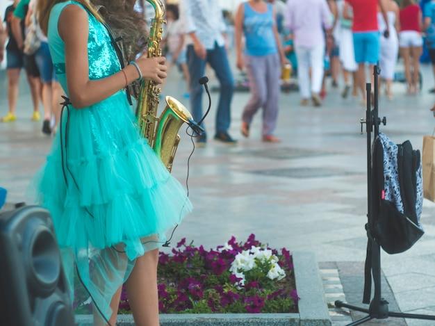 Vista posteriore bambina in piedi nella strada affollata e riproduzione di musica sassofono