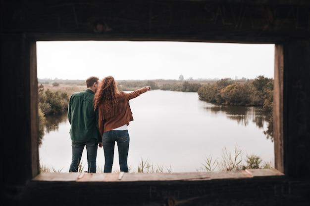 Vista posteriore coppia cerca in lontananza