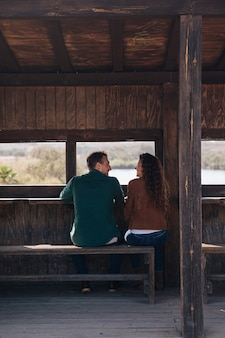 Vista posteriore coppia seduta all'interno di un rifugio