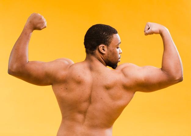 Vista posteriore del bicipite uomo atletico senza camicia