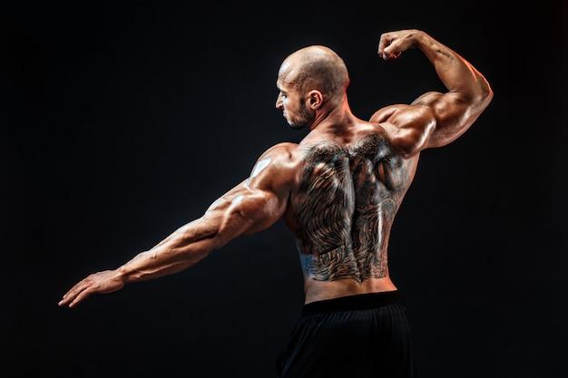Vista posteriore del bodybuilder tatuato con le braccia aperte