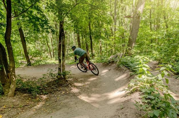 Vista posteriore del ciclista in sella a bici lungo la strada forestale