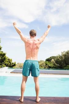 Vista posteriore del giovane in piedi vicino a bordo piscina