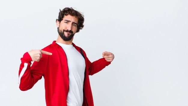 Vista posteriore del giovane uomo barbuto che sembra fiero, positivo e casuale che indica il petto con entrambe le mani sopra la parete dello spazio della copia