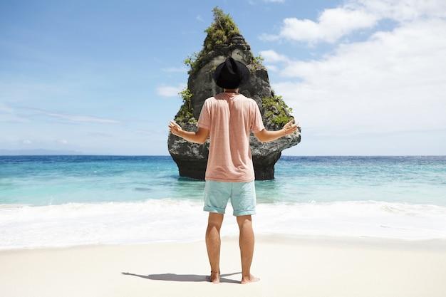 Vista posteriore del giovane viaggiatore con cappello nero in piedi a piedi nudi sulla spiaggia sabbiosa di fronte a una scogliera rocciosa, tenendo le mani tese mentre ammira il bellissimo posto che stava cercando da molto tempo