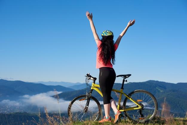 Vista posteriore del motociclista femminile sportivo in piedi con le mani in alto con la bicicletta gialla sulla cima della montagna, indossando il casco, godendo foschia mattutina nella valle.