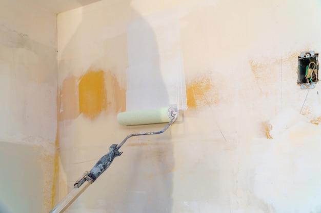Vista posteriore del pittore uomo che dipinge le pareti con rullo di vernice