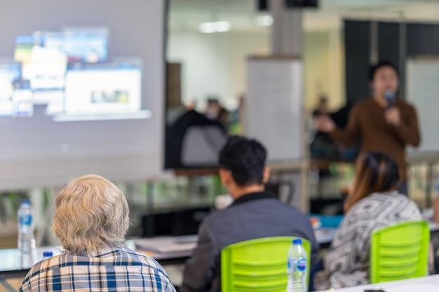 Vista posteriore del pubblico che ascolta l'oratore sul palco nella sala conferenze o seminario