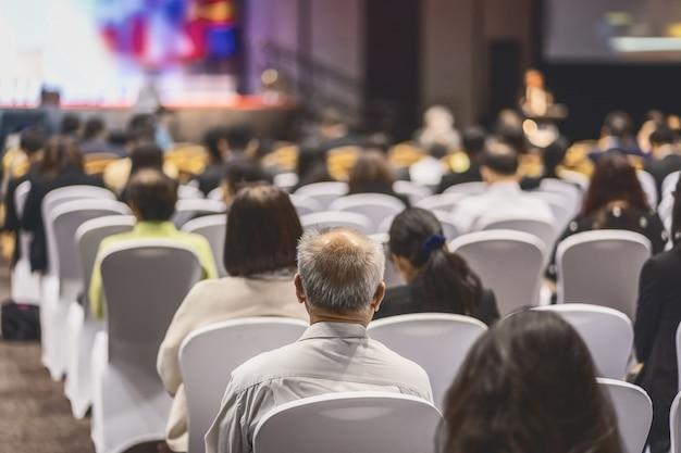 Vista posteriore del pubblico che ascolta relatori sul palco nella sala conferenze o nella riunione del seminario