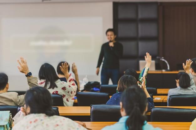 Vista posteriore del pubblico che mostra la mano per rispondere alla domanda del relatore sul palco nella sala conferenze o nella riunione del seminario