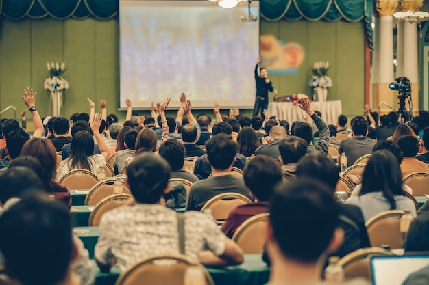 Vista posteriore del pubblico che mostra la mano per rispondere alla domanda dell'altoparlante sul palco