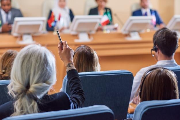 Vista posteriore del pubblico in poltrona che alza le mani per porre domande all'oratore dopo il rapporto alla conferenza
