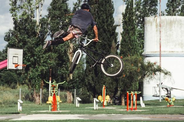 Vista posteriore del ragazzo con stupefacente acrobazia in bicicletta al parco skate