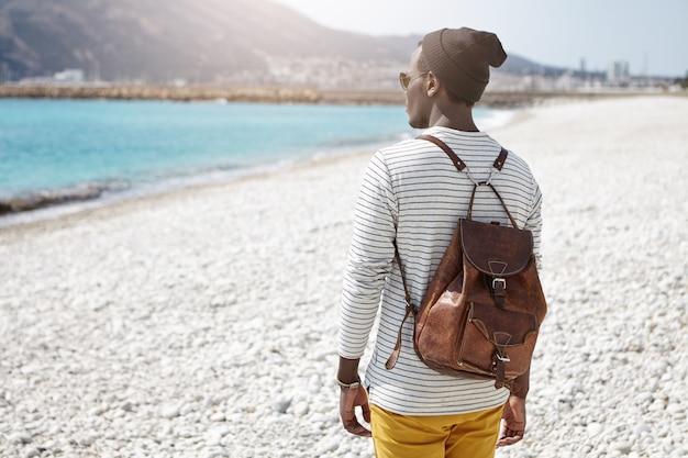 Vista posteriore del viaggiatore con zaino e sacco a pelo africano che affronta il mare in vestiti alla moda, viaggiando da solo nella località turistica europea, ammirando l'acqua e le montagne azzurro cielo, pensando a qualcosa di segreto e intimo