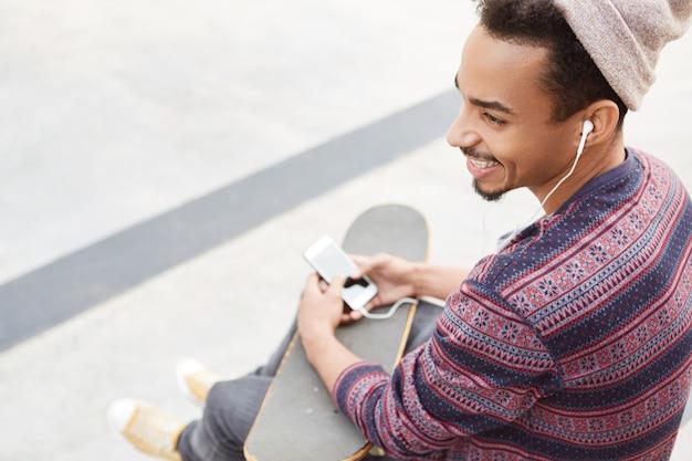 Vista posteriore dell'adolescente dalla pelle scura si siede con lo skateboard all'aperto, ha buon umore dopo aver praticato sport estremi,