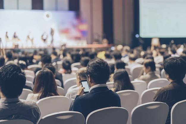 Vista posteriore dell'udienza del pubblico altoparlanti sul palco nella sala delle conferenze o nella riunione del seminario