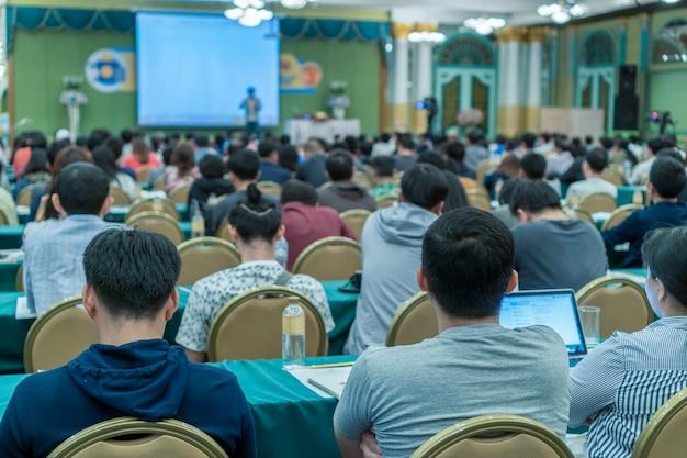 Vista posteriore dell'udienza del pubblico i relatori presentano la diapositiva sul palco nella confere