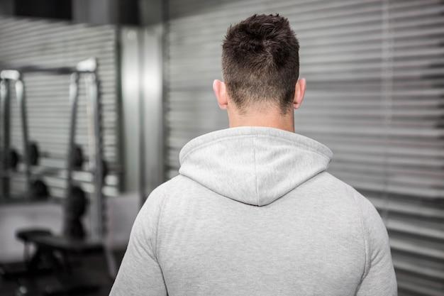 Vista posteriore dell'uomo con un maglione grigio nella palestra di crossfit