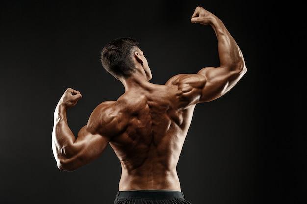 Vista posteriore dell'uomo irriconoscibile, muscoli forti in posa con le braccia in alto