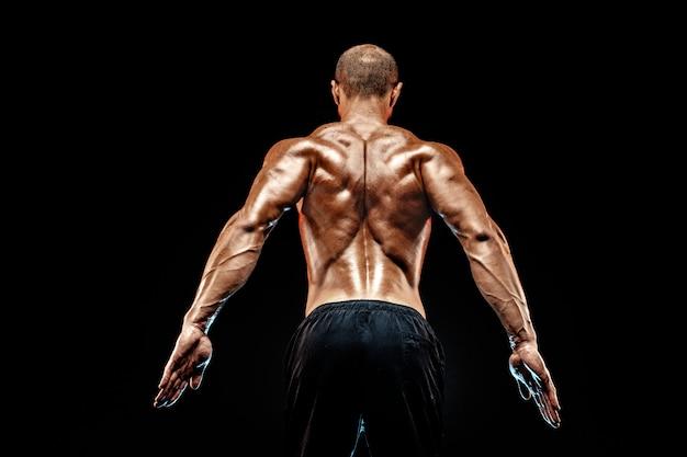 Vista posteriore dell'uomo irriconoscibile, muscoli forti in posa con le braccia verso il basso. isolato