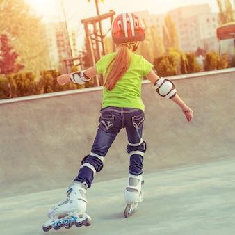 Vista posteriore della bambina in casco sui pattini a rotelle