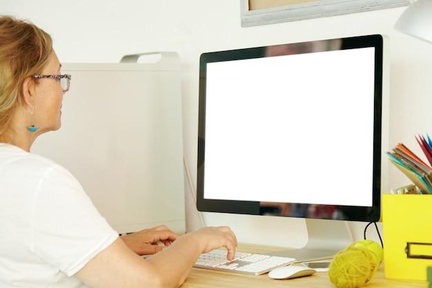 Vista posteriore della bella femmina matura che indossa una maglietta bianca utilizzando il pc con schermo vuoto copia spazio per il testo promozionale o il contenuto pubblicitario, pagamento delle bollette domestiche online, controllo della posta elettronica