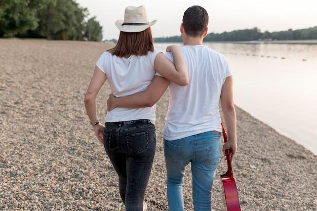 Vista posteriore della coppia abbracciando e camminando in riva al lago