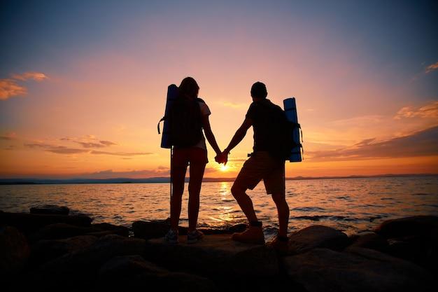 Vista posteriore della coppia che gode del tramonto