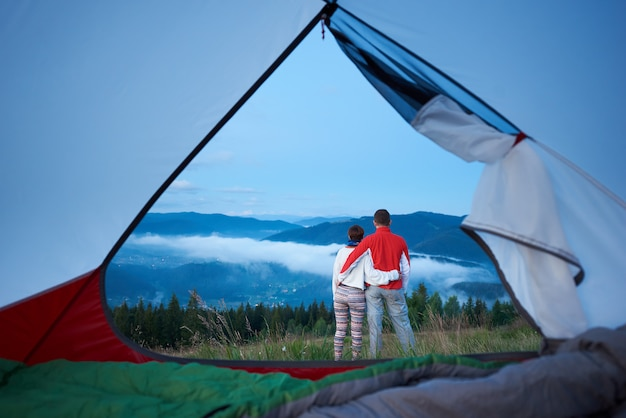 Vista posteriore della coppia dolce in piedi abbracciati ammirando la vista delle montagne nella foschia leggera del mattino. vista dall'interno di una tenda