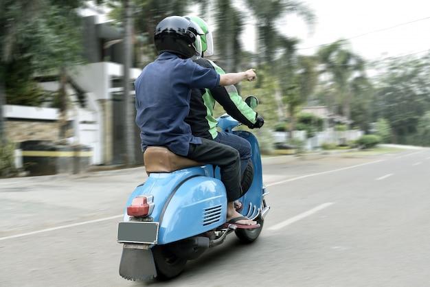 Vista posteriore della direzione spettacolo passeggeri per autista di taxi moto