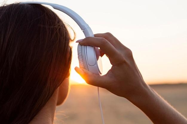 Vista posteriore della donna ammirando il tramonto con le cuffie