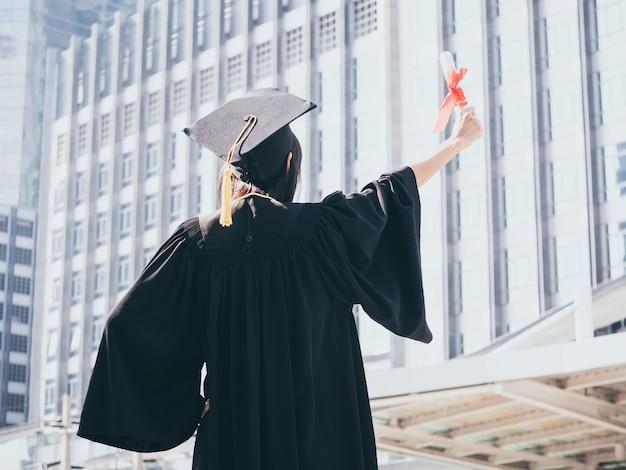 Vista posteriore della donna asiatica con cappello di laurea e abito in possesso di diploma