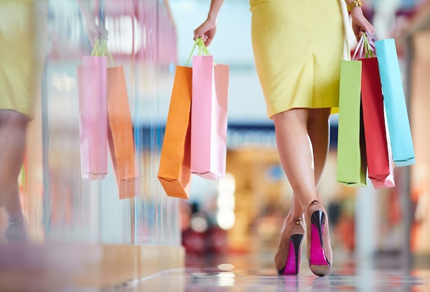 Vista posteriore della donna che cammina attraverso il centro commerciale
