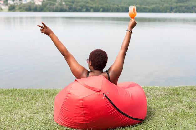 Vista posteriore della donna che gode del cocktail all'aperto sul sacchetto di fagioli
