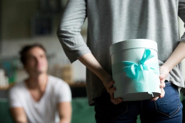Vista posteriore della donna che nasconde il presente facendo sorpresa per il fidanzato
