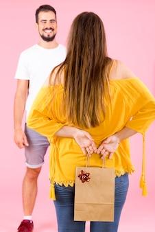 Vista posteriore della donna che nasconde il sacchetto di carta commerciale con fiocco rosso dal suo fidanzato