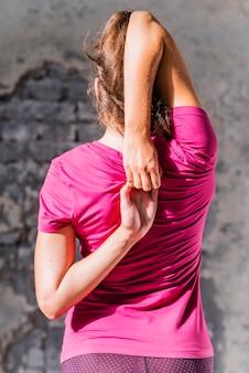 Vista posteriore della donna in forma facendo gomukhasana in classe di yoga