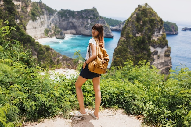 Vista posteriore della donna in viaggio in piedi su scogliere e spiaggia tropicale