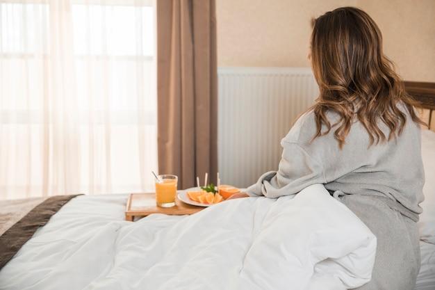Vista posteriore della donna seduta sul letto con la colazione sana