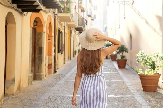 Vista posteriore della donna turistica che cammina nella città vecchia di cefalù in sicilia, italia