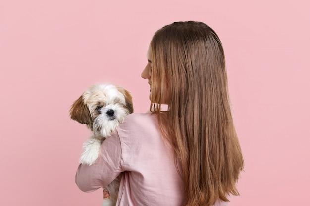 Vista posteriore della femmina con lunghi capelli scuri, porta il piccolo cane birichino, gioca e passa del tempo insieme, andando a fare una passeggiata all'aperto, isolato sul rosa. la donna tiene piccolo animale domestico al coperto