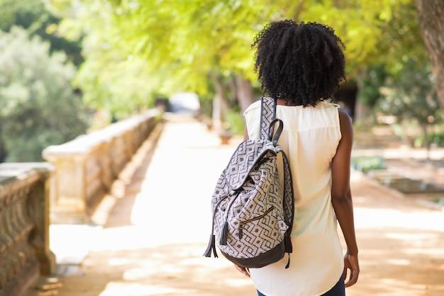 Vista posteriore della femmina turistica con lo zaino a piedi