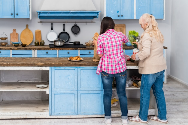 Vista posteriore della figlia e sua madre senior preparare il cibo in cucina
