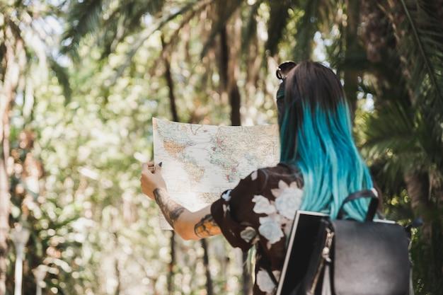 Vista posteriore della giovane donna alla ricerca di destinazione nella mappa